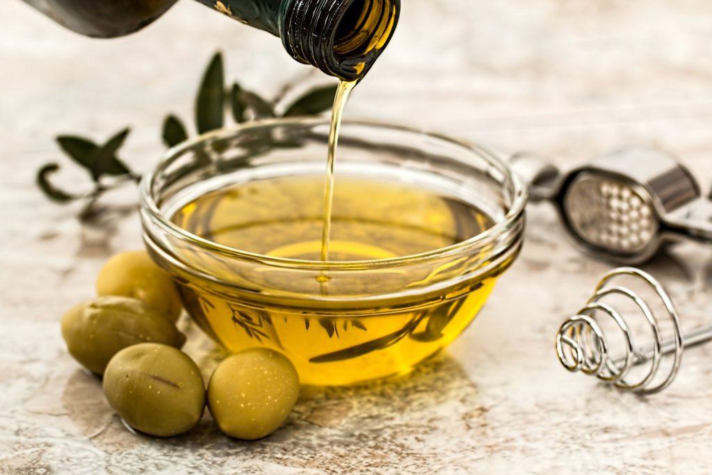Huile d'olive versée dans un bol transparent posé à côté d'olives vertes et d'ustensiles de cuisine