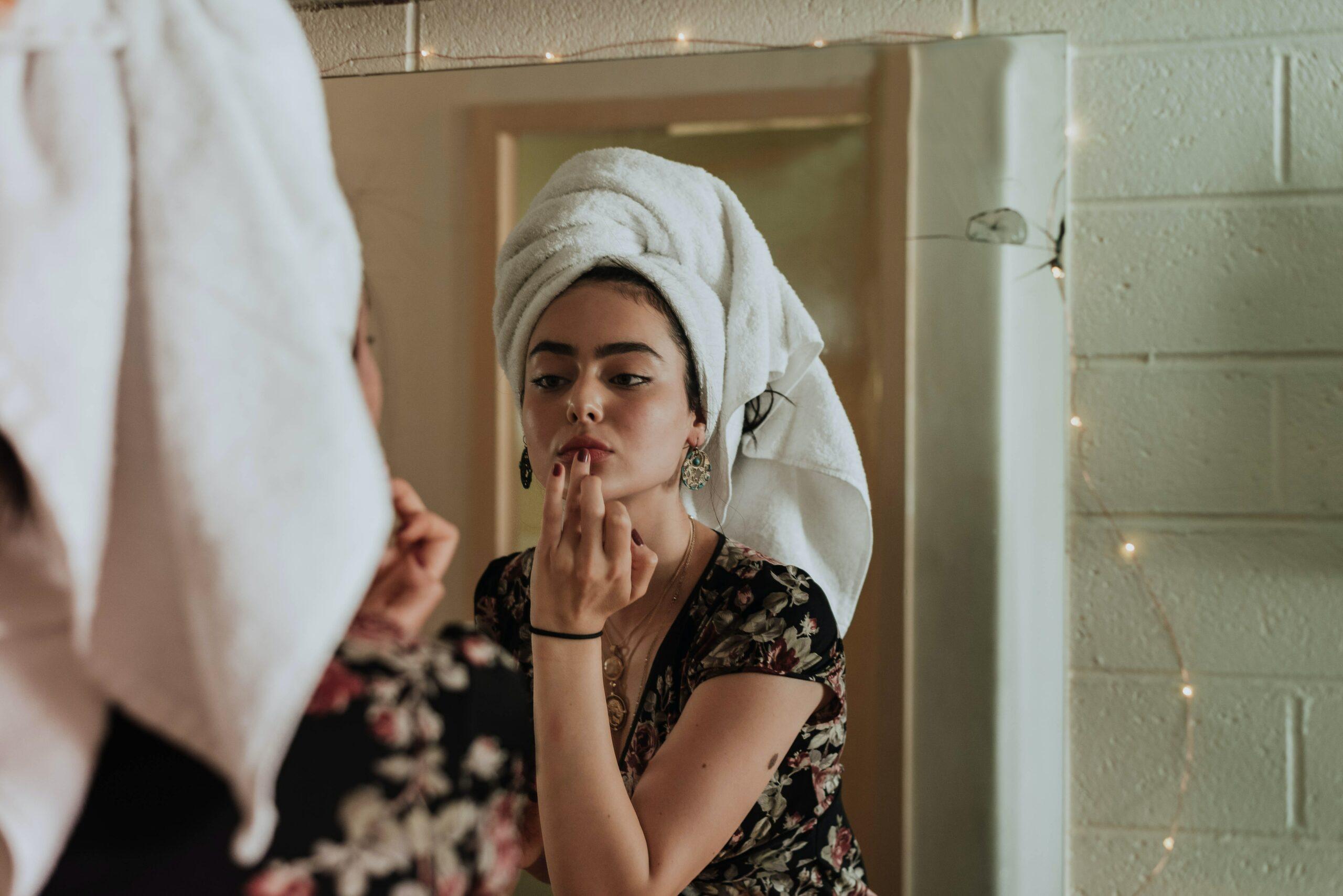Jeune femme qui se démaquille face au miroir