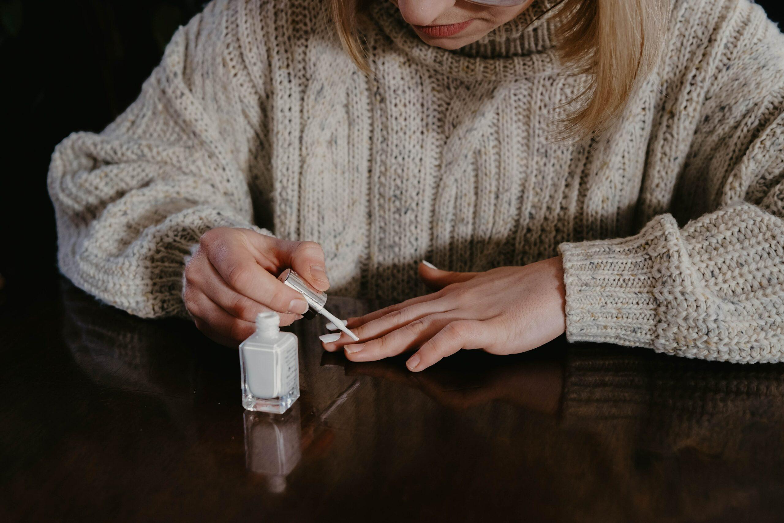 Jeune femme qui se met du vernis blanc sur les ongles
